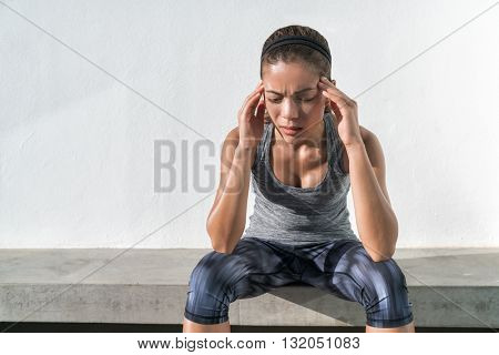 Athlete fitness running woman with headache migraine pain during cardio workout run. Asian athlete w