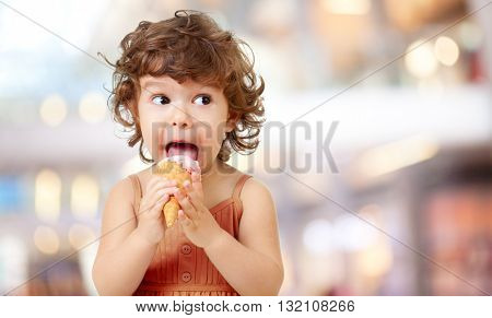 Kid eating ice cream in cafe. Funy curly child with icecream outdoor.