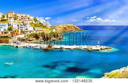 Harbour with marine vessels boats and lighthouse. Panoramic view from a cliff on a Bay with a beach and architecture Bali - vacation destination resort with secluded beaches and clear turquoise ocean waters Rethymno Crete Greece