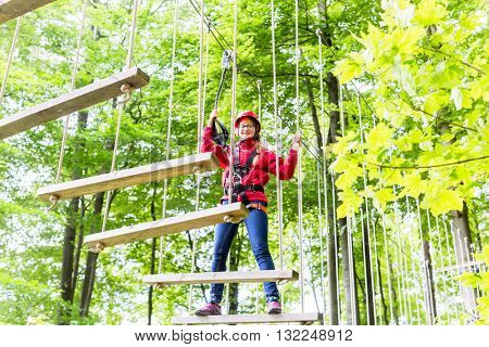 Teenage girl, walking on rope bridge in climbing course enjoying the trill of the sport stock photo