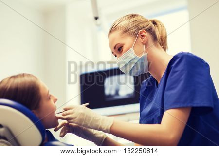 people, medicine, stomatology and health care concept - happy female dentist with mirror or dental p