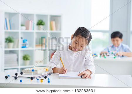 Vietnamese schoolgirl drawing in her textbook in class