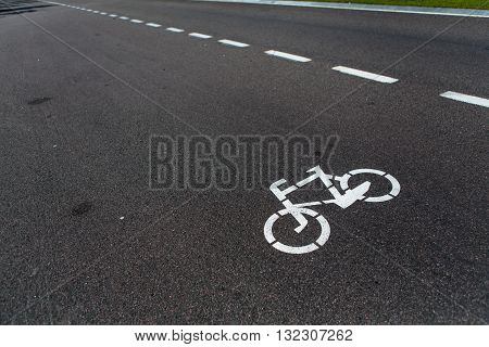 Pathway for bicycle with white bicycle lane sign on road. Bicycle sign path on road, bikes\' lane on outskirts or urban area.