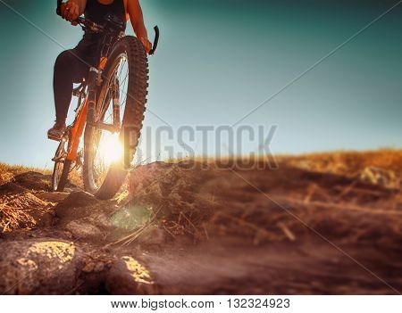 a woman riding a bicycle down a dirt trail with big rocks in the back country to get away from the c