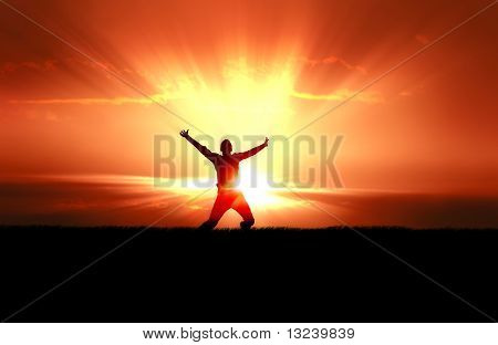 Silhouette of jumping man in field of grass, bright sun behind stock photo