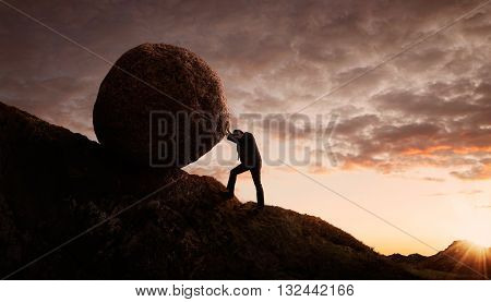 Business concept Young businessman pushing large stone uphill with copy space
