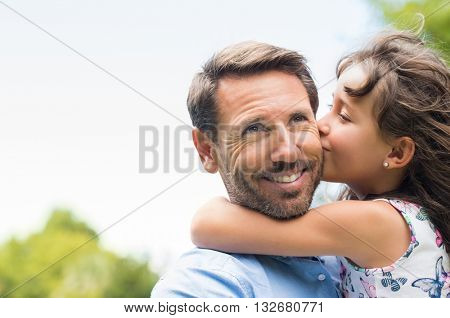 Portrait of a little girl kissing her dad on cheek. Pretty girl giving a kiss to her father outdoor.