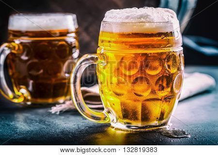 Beer. Two cold beers. Draft beer. Draft ale. Golden beer. Golden ale. Two gold beer with froth on top. Draft cold beer in glass jars in pub hotel or restaurant. Still life.