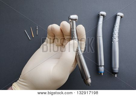 Hand of dentist in latex protective gloves holding dental drill handpiece. Flat lay of dental handpiece in dentist hand on gray background. Dental handpieces and bur tools on background stock photo