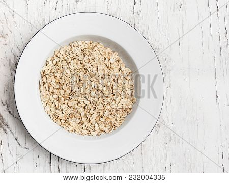 Oatmeal, rolled oats on white wooden table. Porridge oats, used in granola or muesli. Copyspace, flat lay stock photo