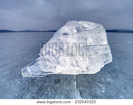 Ice floe and crushed ice on dark frozen and flat  ground. Shining crushed ice in strong colorful backlight. stock photo