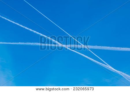 Bright blue sky with white lines, traces of aircraft. The lines are straight and intersect. Three lines. Three trajectories. stock photo