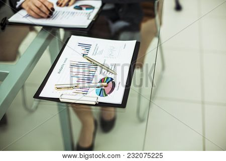 workplace business team: financial charts and pens lying on the glass table in the office. stock photo