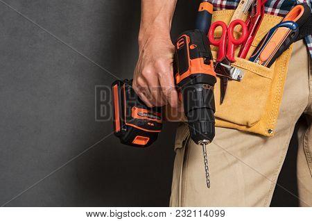 Close up of handyman holding a drill machine with tool belt around waist. Detail of artisan hand hol