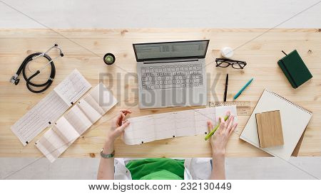 Professional female doctor cardiologist or neurologist analyzing a cardiogram of patients and writing medical records on laptop and medical equipment all around, desktop top view with copy space. stock photo