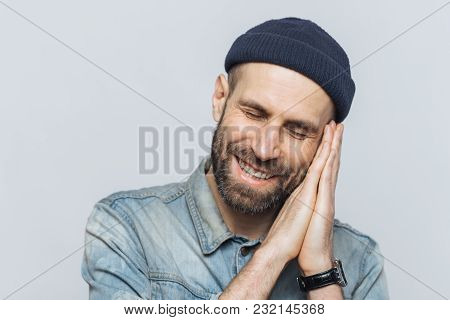 Positive bearded male pretends sleeping, has pleasant dreams, rests on hands, smiles joyfully, wears black stylish hat, isolated over white background. People, good rest and emotions concept. stock photo