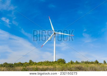 Rotating windmill generating renewable energy with wind power. Sustainability by windmills turbines preventing climate change with regenerative clean green nature energy. Windy blue sky with clouds stock photo