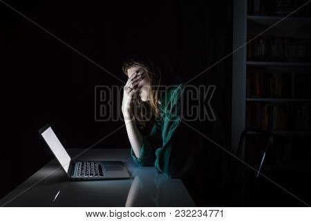 Tired And Exhausted Young Woman Hides Eyes With Hand At Laptop Pc Late In The Evening. Portrait Of D
