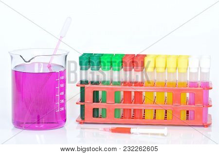 Set of chemical test tubes with different colors chemicals and chemical beaker with permanganate dissolved in water, pipette and syringe stock photo