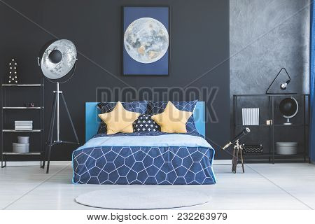 Knit blanket on patterned bedsheets of bed next to a lamp, against white wall with poster in bedroom interior stock photo