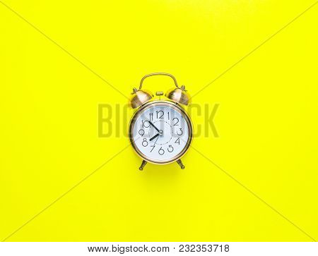 Alarm Clock Showing Eight O'Clock on Bright Yellow Background. Flat Lay. Morning Sunlight. New Day Beginning Waking Up Energy Concept. Copy Space Mock Up Template stock photo