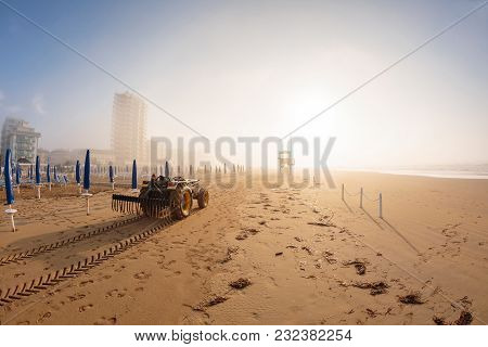 tractor on the sandy beach cleaning, after winter, preparation for the holiday season in Italy. Wooden trunks in on the seashore after a sea storm stock photo