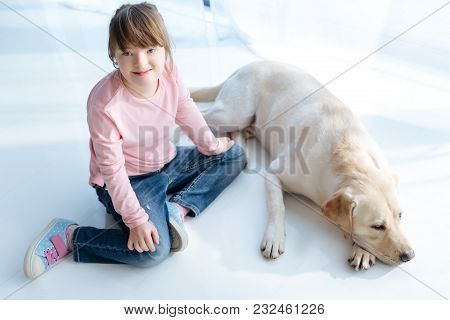 Top view of child with down syndrome and dog retriever in room stock photo