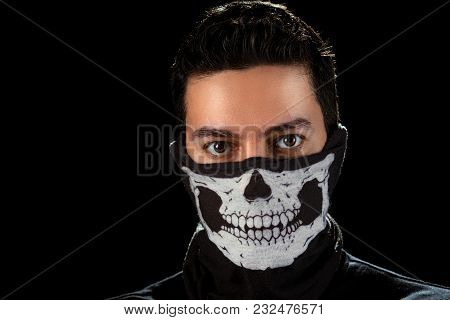 Closeup portrait of the man with expressive eyes in the mask with skull - anonymous rebel. Isolated on the black background. stock photo