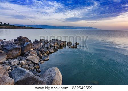 Landscape of rocky shoreline with tranquil waves and sun going down on lake Kinneret, Israel. stock photo