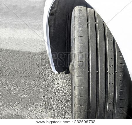 Badly worn out car tire tread and damaged bulb like side due to wear and tear or because of poor tracking or alignment of the wheels, dangerous for driving, unsafe, not safe for use, copy space. stock photo