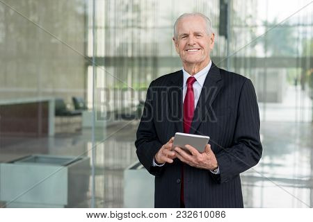 Closeup portrait of smiling senior business man looking at camera and using tablet computer in office lobby. Successful senior business man concept. Front view. stock photo