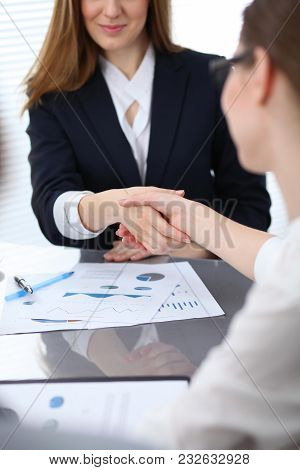 Close Up of unknown business people shaking hands while finishing up a meeting. Handshaking, agreement or success concept in people communication. stock photo