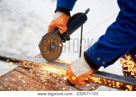 Cropped close up of an industrial worker in protective uniform and gloves cutting metal sawing welding iron outdoors in winter factory industry metalworking electric sparks steel profession. stock photo