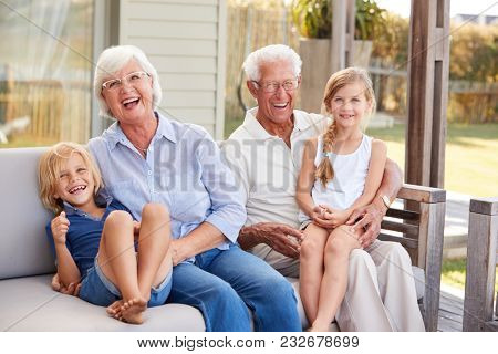 Grandparents With Grandchildren Relaxing On Deck At Home stock photo