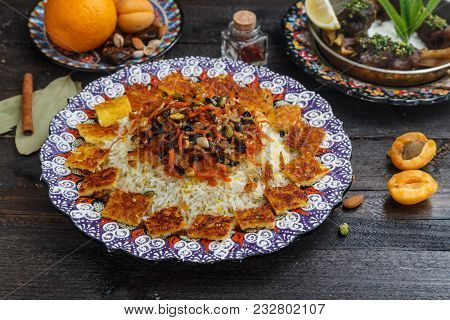 Iranian pilaf with orange zest, nuts and raisins, on a traditional plate. stock photo