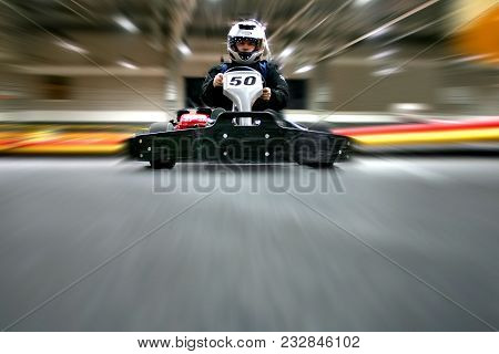 The man is going on the go-kart on karting track indoors. He is wearing a helmet. stock photo