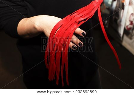 whip red, sex toy in female hands stock photo