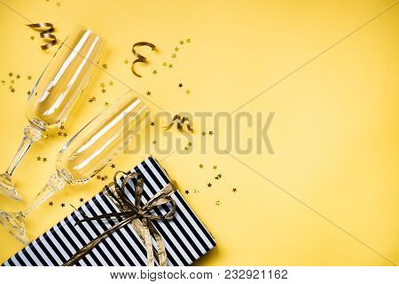 Celebration background - top view of two chrystal champagne glasses, a gift box wrapped in black and white striped paper, ribbons and star shaped golden confetti over yellow background. Copy space. stock photo