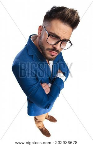 smart casual man with arms crossed puts on serious face while standing on white background, full body picture stock photo