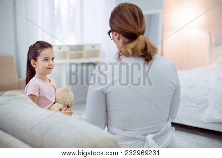 Describe your state. Charming confident girl looking at female doctor sitting on sofa and talking to her stock photo