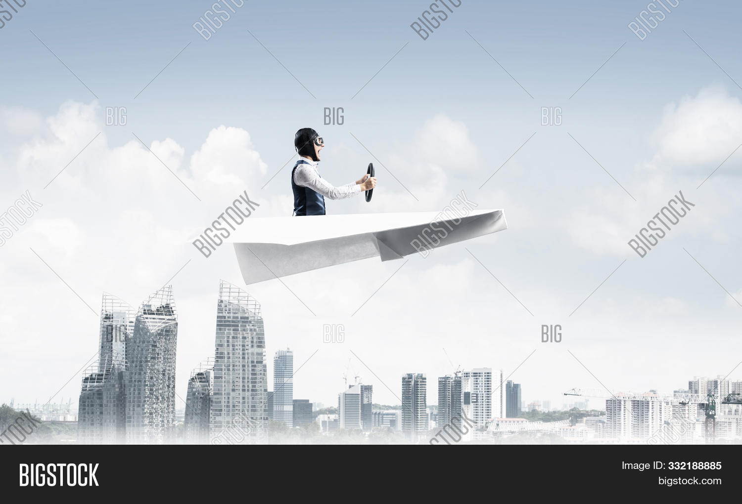 Businessman in aviator hat and goggles driving paper plane above downtown with high buildings. Modern megalopolis panorama with blue skyscape. Mixed media business concept. Dreaming and imagination.