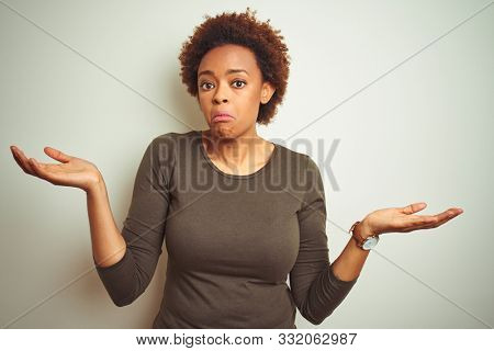 Young beautiful african american woman with afro hair over isolated background clueless and confused expression with arms and hands raised. Doubt concept. stock photo