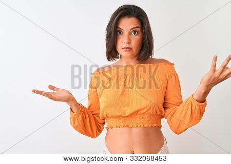 Young beautiful woman wearing orange t-shirt standing over isolated white background clueless and confused expression with arms and hands raised. Doubt concept. stock photo