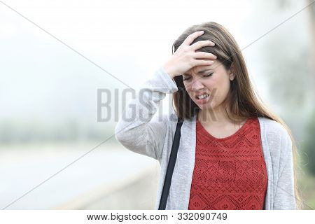 Front view portrait of an woman complaining suffering head ache a foggy day stock photo