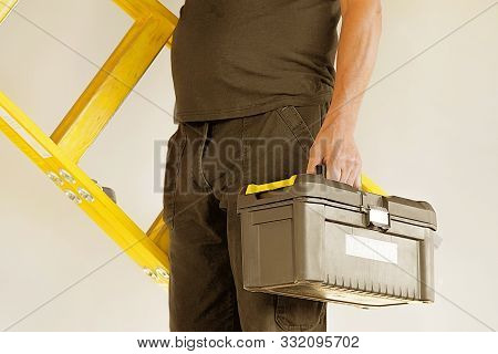 Electrician holds tool box and yellow wooden ladder. The builder carries a wooden ladder and toolbox on a gray background. Breeder with tool box and yellow wooden ladder. stock photo