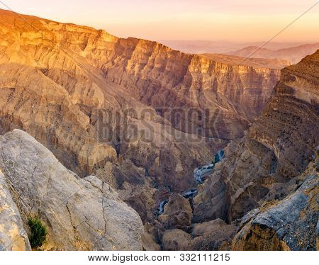 Panoramic view of Wadi Ghul aka Grand Canyon of Arabia in Jebel Shams, Oman at sunset stock photo