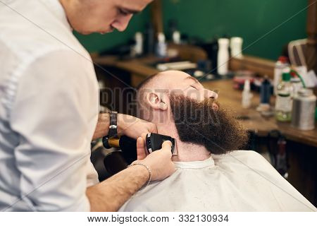 Bearded man client in hairdresser chair throwing back his head during barber styling clients beard with shaver machine. Professional tools, accessories and care products on blurred background. stock photo