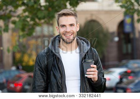Happy morning. Hipster hold paper coffee cup. Coffee break. Drink it on go. Man smiling cheerful hipster hold coffee take away. Student guy drink coffee outdoors. Rituals determine personality. stock photo