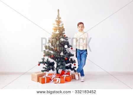 holidays and winter childhood concept - smiling teen boy standing near christmas tree on white background stock photo