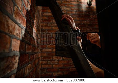 BDSM Close-up of hands in handcuffs. The man dominates and rivets his mistress to the Andreev cross. Games for adults. Brick wall. Red room. stock photo